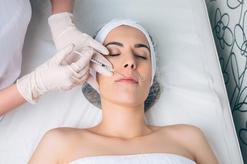 Femme réussissant l'injection cosmétique dans son visage image libre de droits