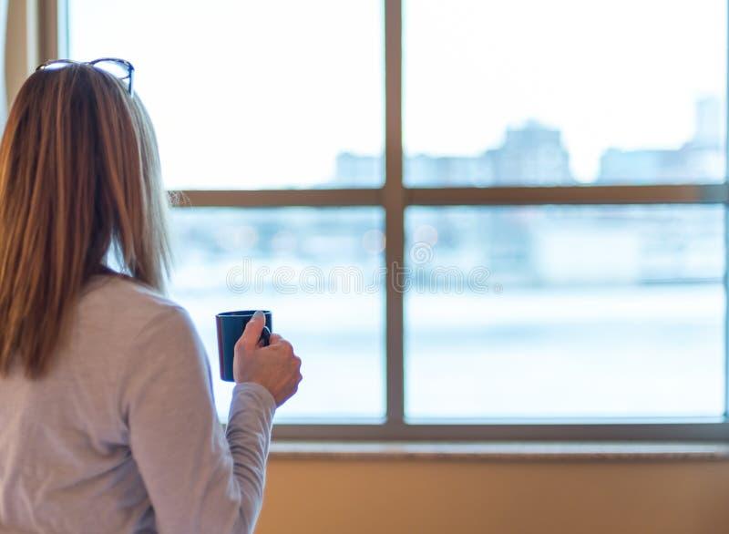 Femme réveillant et regardant la fenêtre d'hôtel avec du café à disposition photos stock