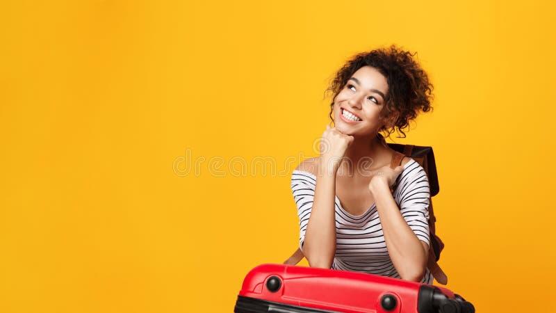 Femme rêveuse d'Afro pensant aux vacances, fond orange photographie stock