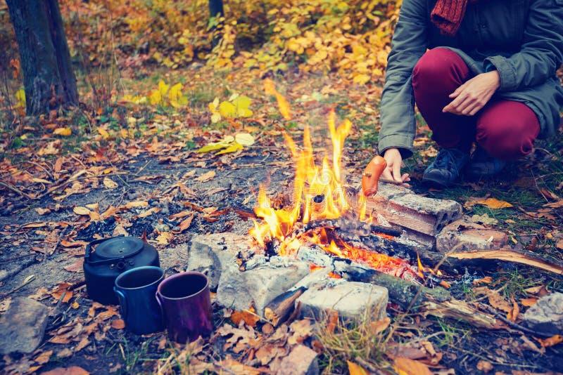 Femme rôtissant une saucisse sur un feu photo stock
