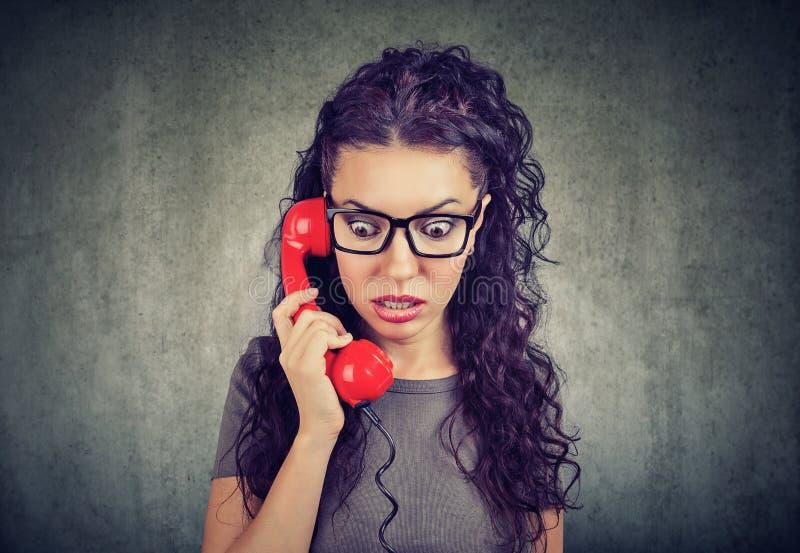 Femme recevant des actualités choquantes à un téléphone se sentant soucieux images libres de droits