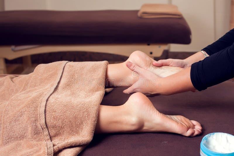 Femme recevant et appréciant un massage de pied au salon de station thermale photo stock