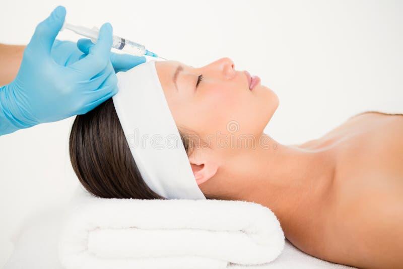 Femme recevant l'injection de botox sur son front image stock