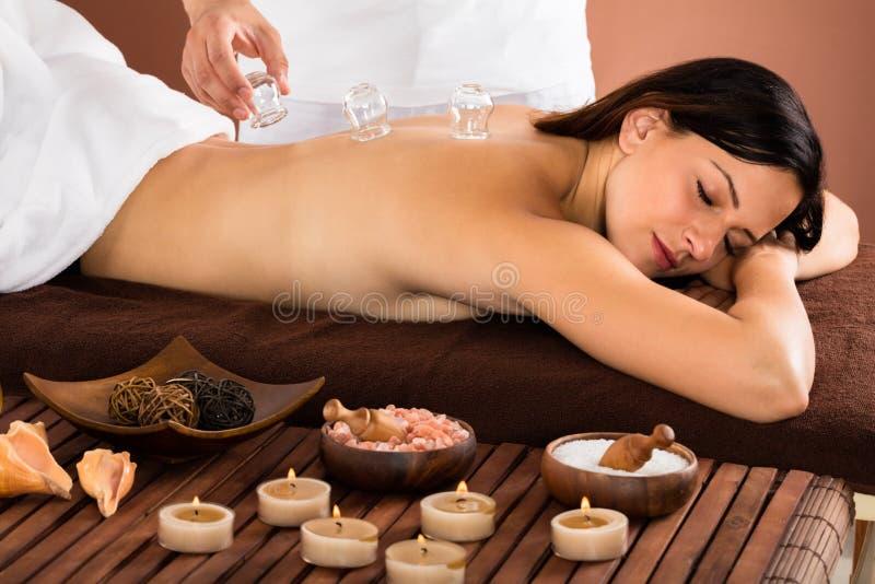 Femme recevant le dos mettant en forme de tasse de traitement dessus photo stock