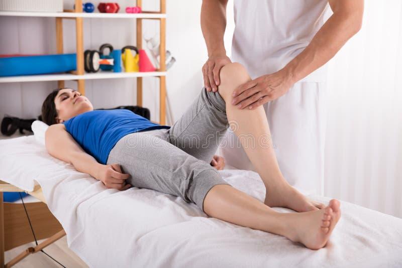Femme recevant le massage de jambe image stock