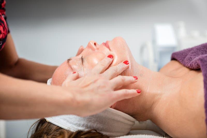 Femme recevant le massage de visage dans le salon de beauté images libres de droits
