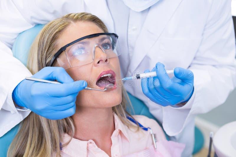 Femme recevant le traitement dentaire à la clinique médicale photos stock