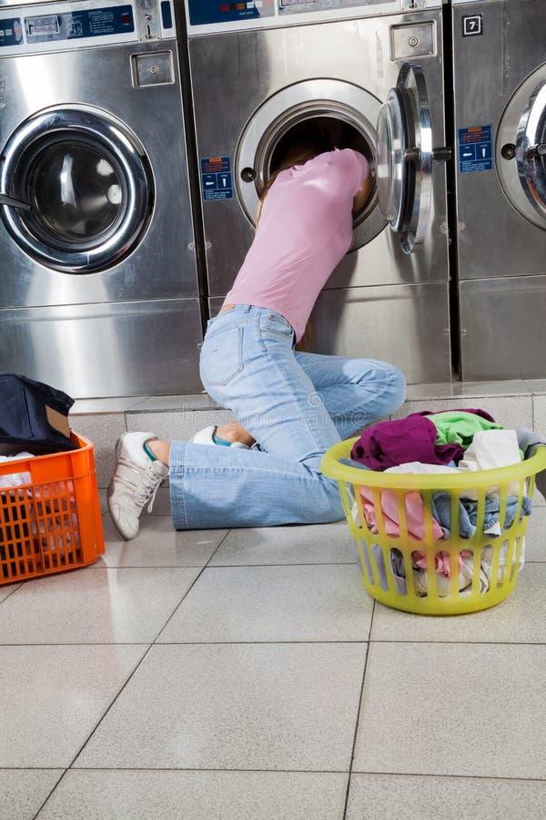 Femme recherchant des vêtements dans le fût de machine à laver photographie stock