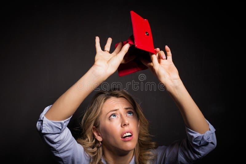 Femme recherchant l'argent dans son portefeuille photographie stock libre de droits