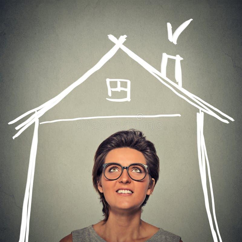 Femme recherchant le toit de maison au-dessus de la tête photographie stock