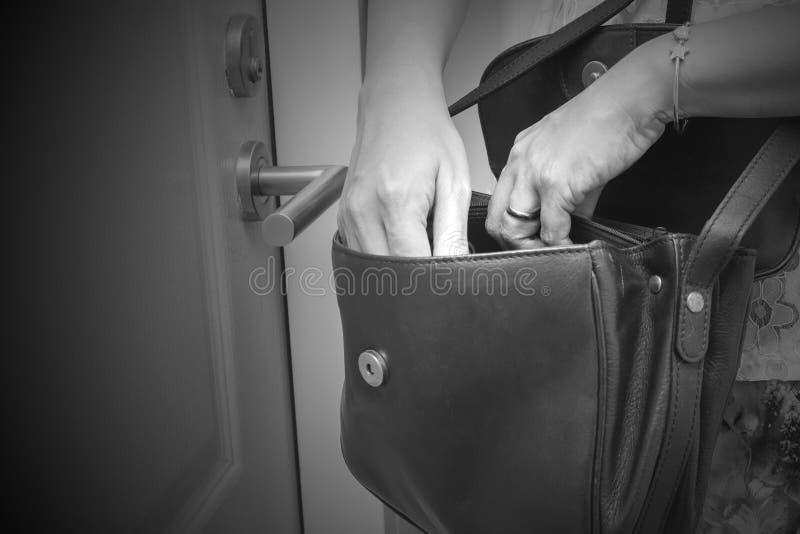 Femme recherchant quelque chose telle que des clés dans son sac à main devant son appartement Ton noir et blanc photographie stock libre de droits