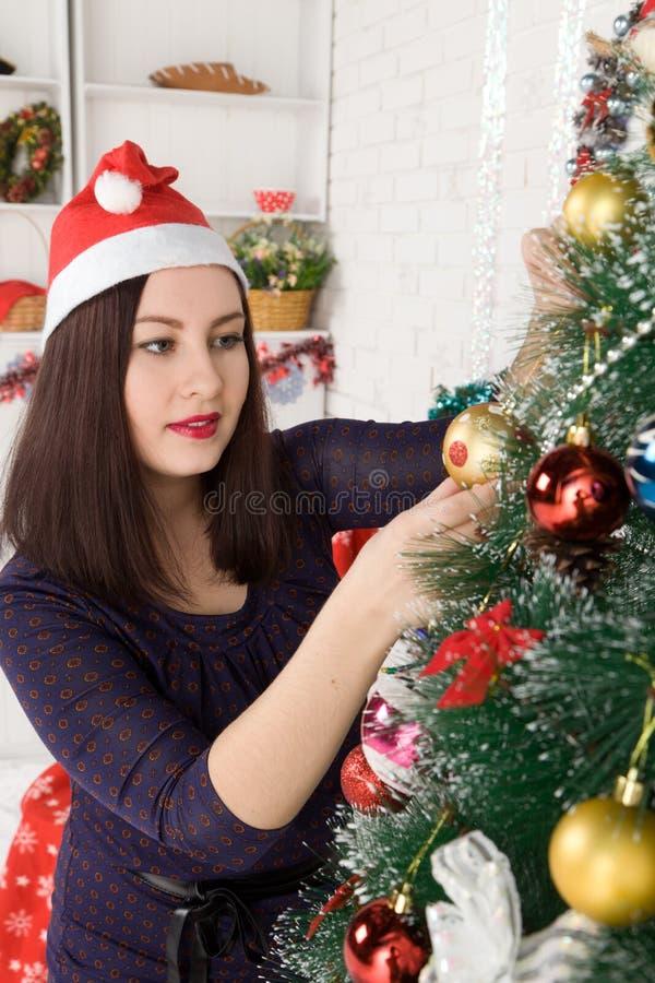 Femme rectifiant l'arbre de Noël image libre de droits