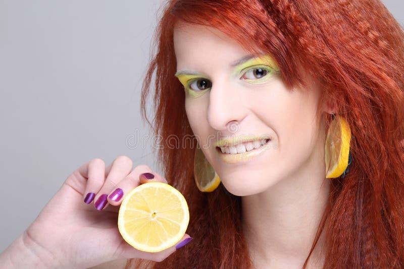 Femme Redhaired avec des boucles d oreille de citron