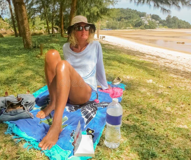 Femme refroidissant sur le rivage vert photo stock