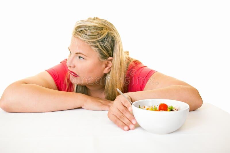 Femme regardant à partir du bol de salade saine images stock