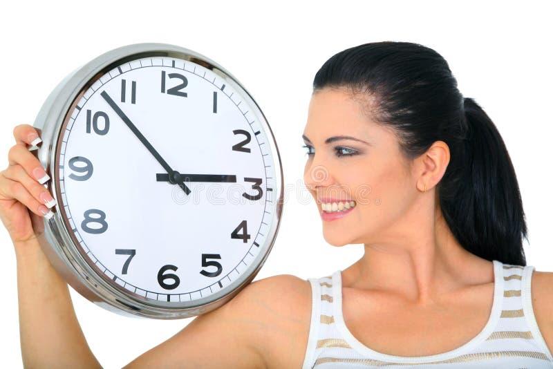 Femme regardant au-dessus de l'horloge photographie stock libre de droits