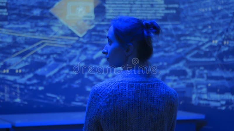 Femme regardant autour et présentation visuelle de observation sur le grand affichage image libre de droits