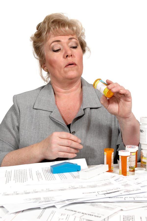 Femme regardant dans la bouteille de médecine photos stock