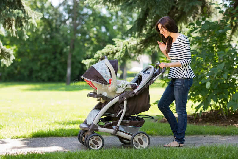 Femme regardant dans la voiture d'enfant en parc photos stock