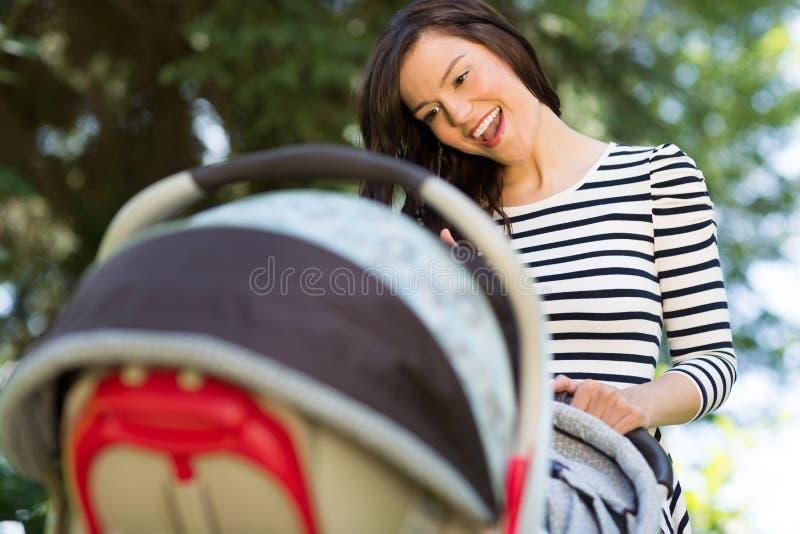 Femme regardant dans la voiture d'enfant en parc image libre de droits