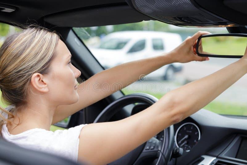 Femme regardant dans la voiture de miroir de vue arrière photos stock