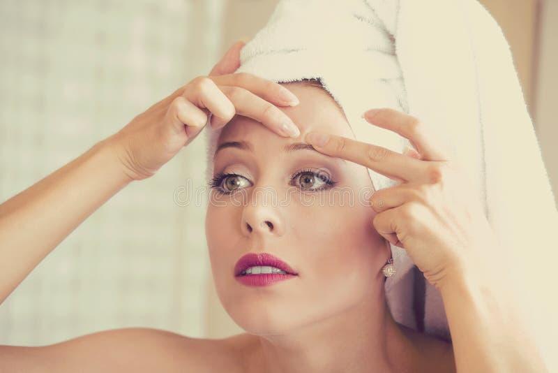 Femme regardant dans le miroir serrant l'acné ou le point noir sur le visage image libre de droits