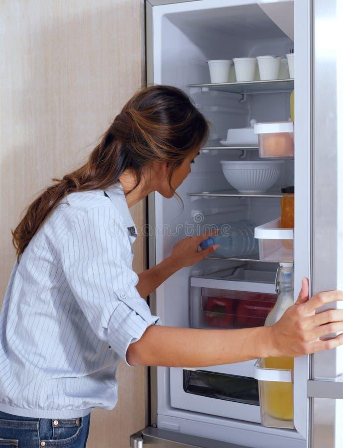 Femme regardant dans le réfrigérateur photos stock