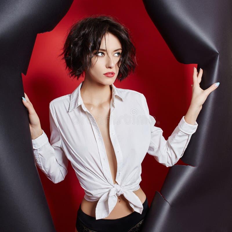 Femme regardant dans le trou, le beau maquillage lumineux, les grands yeux et des lèvres, rouge à lèvres lumineux, cosmétiques pr photo libre de droits
