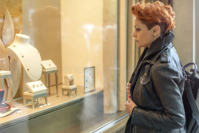Femme regardant dans une fenêtre de boutique avec des bijoux images libres de droits