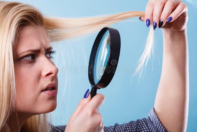 Femme regardant des cheveux par la loupe image stock