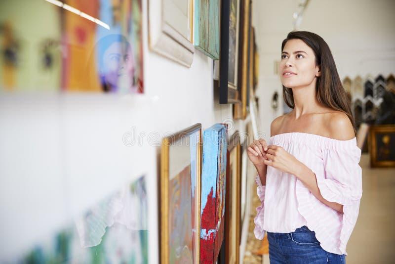 Femme regardant des peintures en Art Gallery image stock