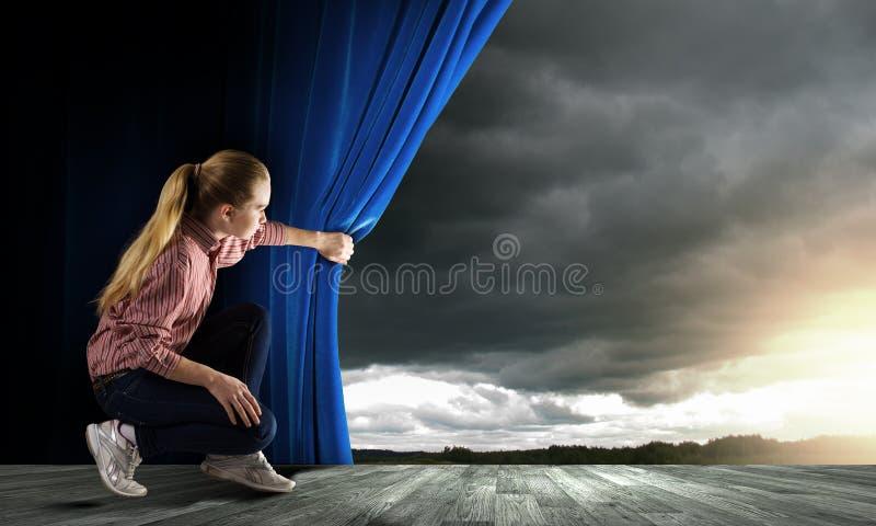 Femme regardant du rideau photo stock