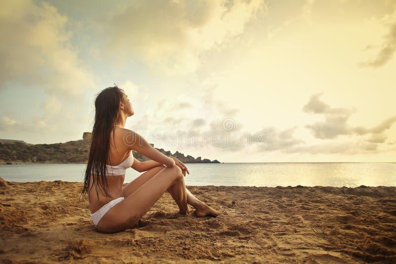 Femme regardant fixement le coucher du soleil photos stock