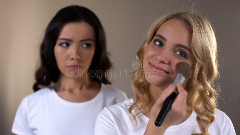 Femme regardant jalousement son bel ami appliquant la poudre de visage, complexe image stock