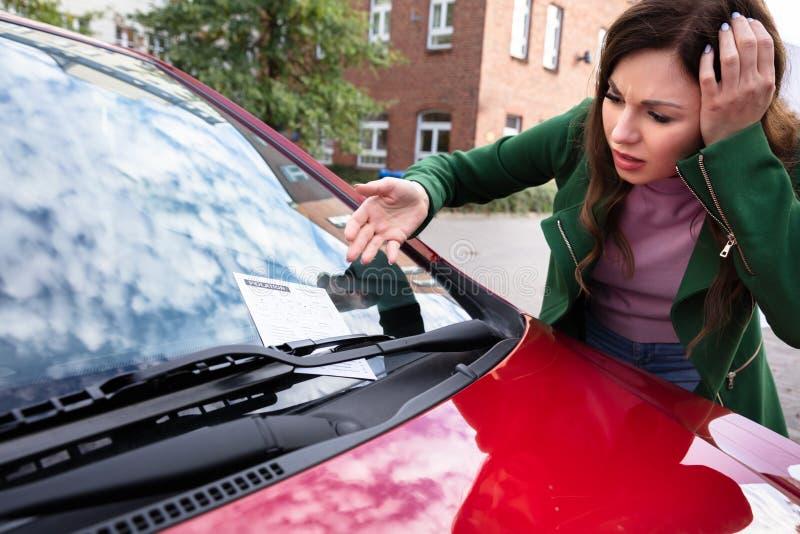 Femme regardant l'amende de billet pour la violation de stationnement sur la voiture photos stock