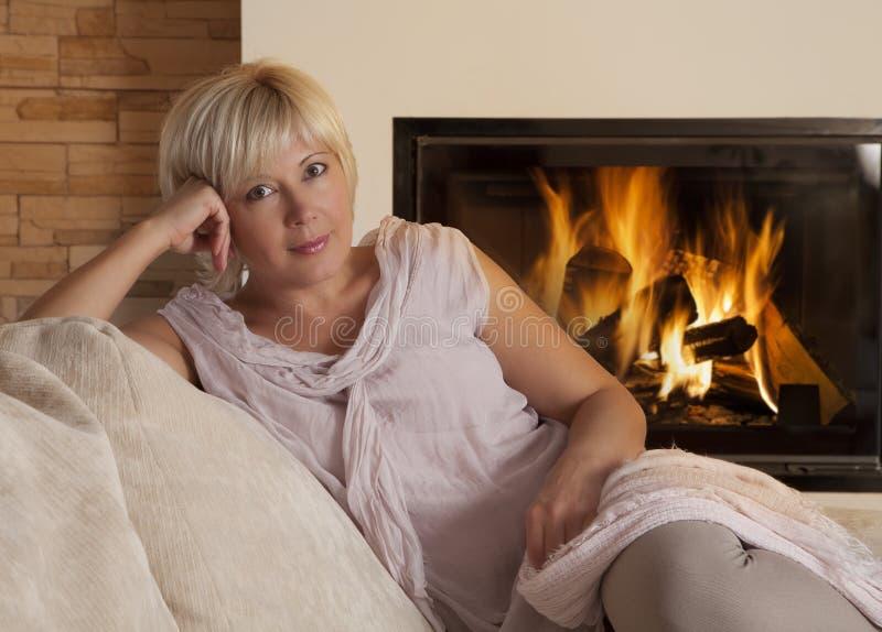 Femme, regardant l'appareil-photo, par la cheminée à la maison photographie stock libre de droits