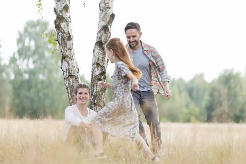 Femme regardant l'homme courant avec la fille sur le champ aux terres cultivables photo stock