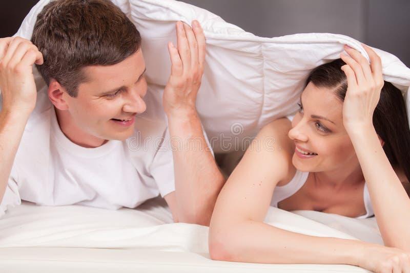 Femme regardant l'homme et se situant dans le lit photographie stock