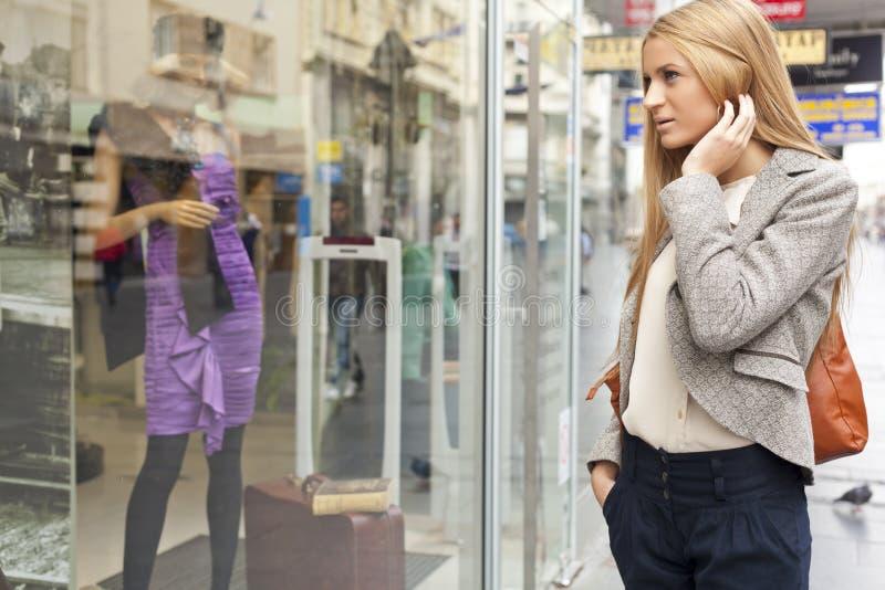 Femme regardant l'hublot dans la rue shoping images libres de droits