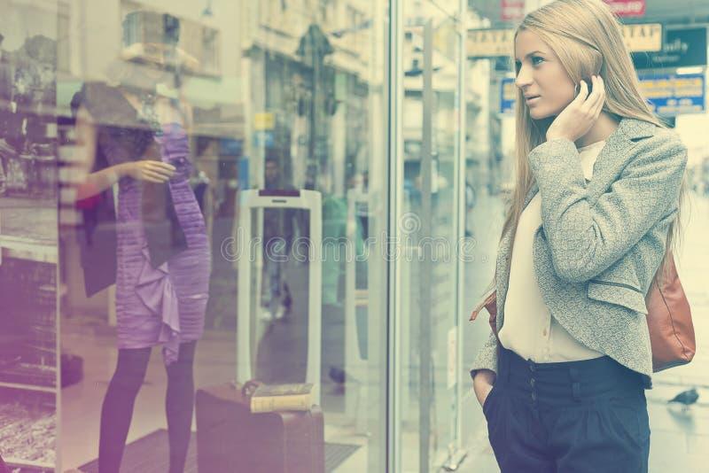Femme regardant l'hublot dans la rue shoping photos stock
