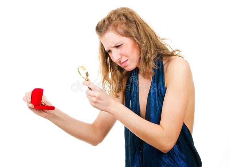 Femme regardant la boucle par la loupe photos stock
