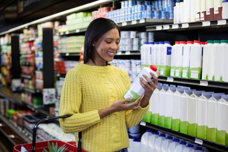 Femme regardant la bouteille à lait dans la section de laiterie photo stock