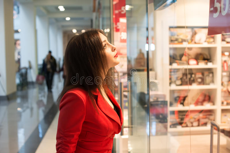 Femme regardant la fenêtre de boutique photos stock