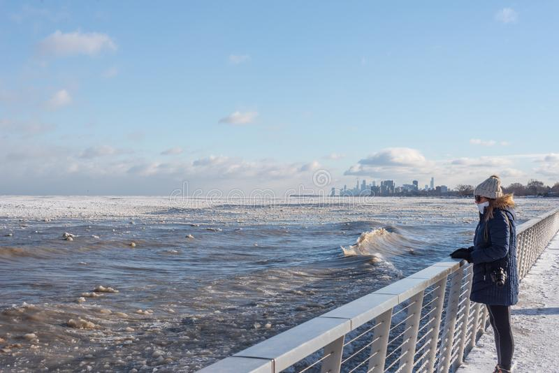 femme regardant la glace sur le lac Michigan avec l'horizon de Chicago à l'arrière-plan images stock