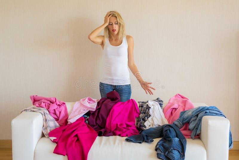 Femme regardant la pile malpropre de vêtements à la maison image stock