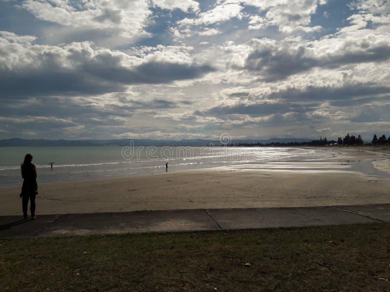 Femme regardant la plage de Waikanae, Gisborne, Nouvelle-Zélande images stock