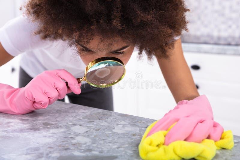 Femme regardant le comptoir de cuisine avec la loupe image libre de droits