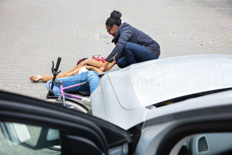 Femme regardant le cycliste masculin inconscient se trouvant sur la rue photographie stock