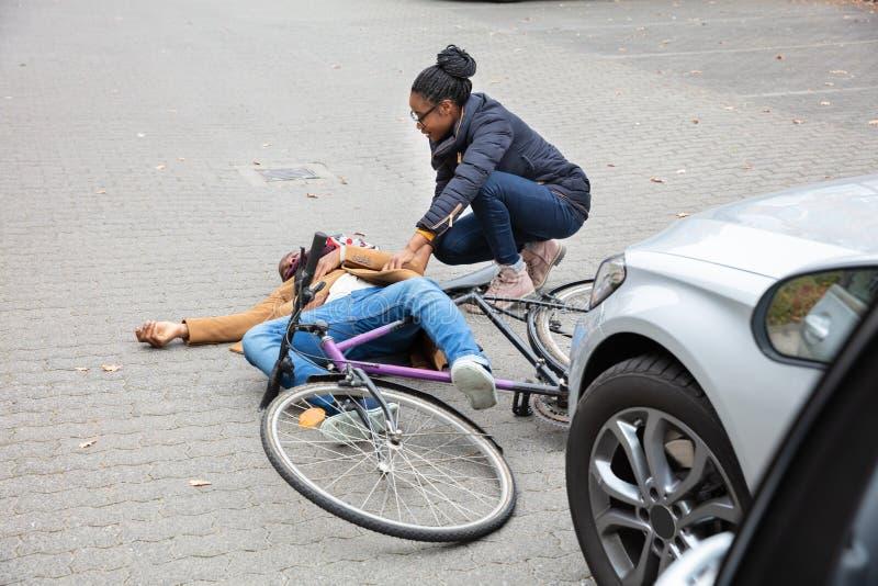 Femme regardant le cycliste masculin inconscient se trouvant sur la rue images stock