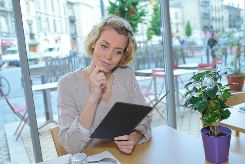 Femme regardant le menu pour la nourriture de commande dans le restaurant photos stock